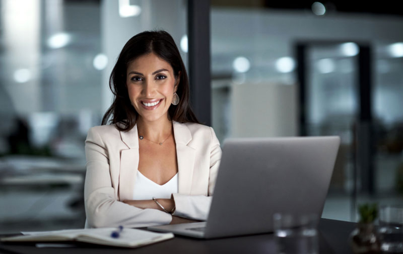 Picture of woman working on laptop, staring at camera