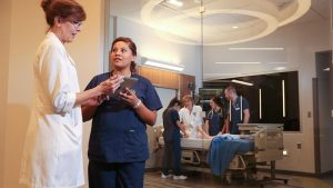 Photo of nursing students practicing in the Health Simulation Center