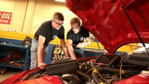 Photo of students working on a car in the Automotive program