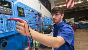 Photo of student working with machine in Industrial Systems Technology