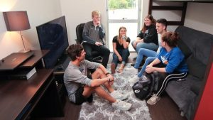 Photo of students lounging in a room of the Campus View Housing Complex