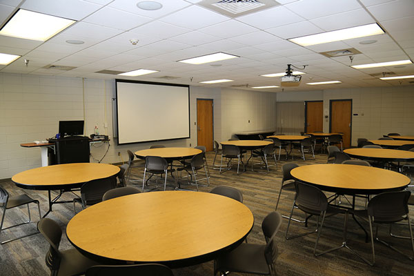 Photo of meeting room AC101 showing tables, chairs, projector, projector screen, and command station