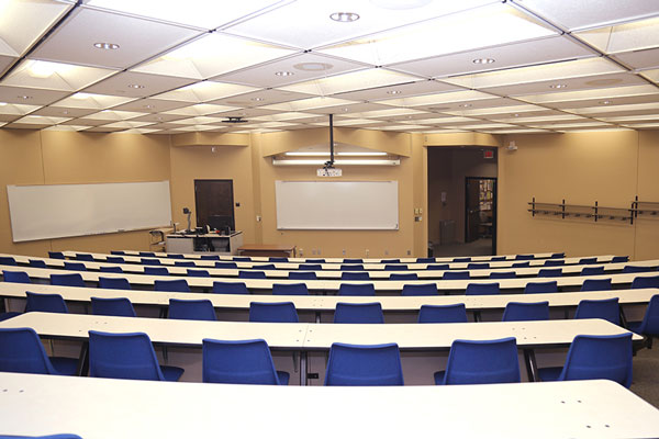 Photo of meeting room MH104G showing projector, white boards, and command station
