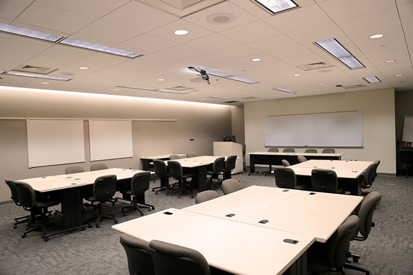 Photo of meeting room PC224 showing tables, desks, projector, white boards, and command station
