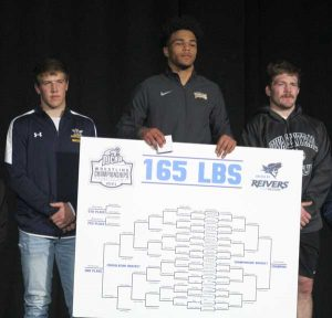 Picture of Wrestling Champion Christian Minto holding 165 pound bracket